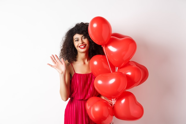 Piękna pani z kręconymi włosami, stojąca w pobliżu świątecznych balonów walentynkowych i machająca ręką, witająca się, stojąca na białym tle.
