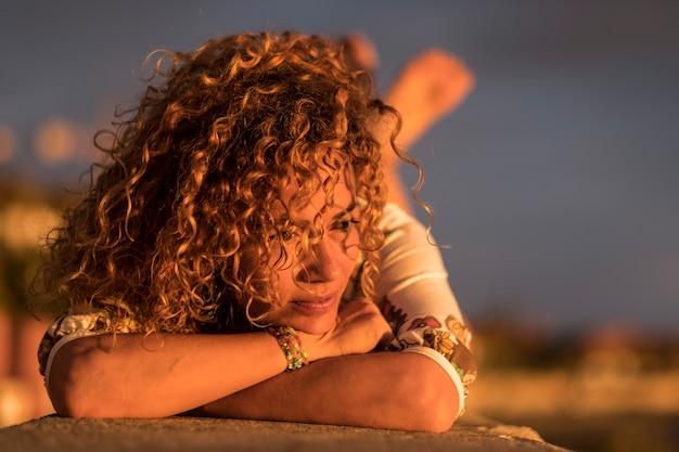 Piękna pani zrelaksowana zamyślona i ciesząca się słońcem na twarzy podczas letniego, ciepłego zachodu słońca. kręcone blond włosy kobieta w średnim wieku. ludzie kaukascy