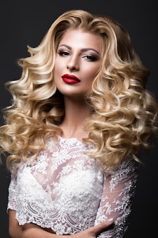 Piękna panna młoda blondynka w obrazie ślubu z loki, czerwone usta. piękna twarz.