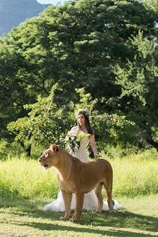 Piękna panna młoda i lwica w malowniczej przyrodzie