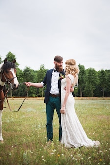 Piękna panna młoda i pan młody hipster stoi obok konia, rustykalny styl