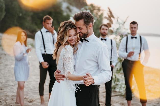 Piękna panna młoda i pan młody na weselu z gośćmi na plaży on