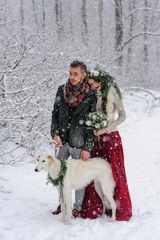 Piękna panna młoda i pan młody z białym psem stoją na tle zaśnieżonego lasu