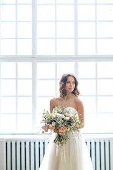 Piękna panna młoda kobieta w eleganckiej sukni ślubnej z bukietem kwiatów