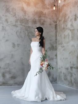Piękna panna młoda kobieta w sukni ślubnej z bukietem kwiatów