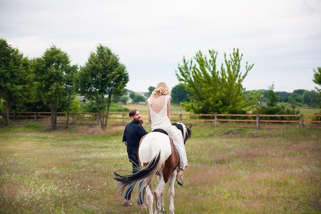Piękna panna młoda na koniu i obok pana młodego hipster, rustykalny styl
