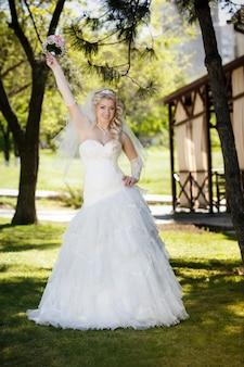 Piękna panna młoda na zielonej trawie w dniu ślubu