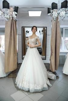 Piękna panna młoda pozowanie w sukni ślubnej w salonie