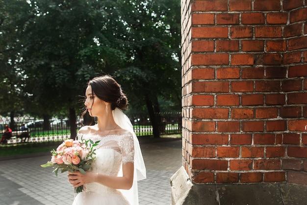 Piękna panna młoda pozuje blisko czerwonej ściany stary gotycki kościół