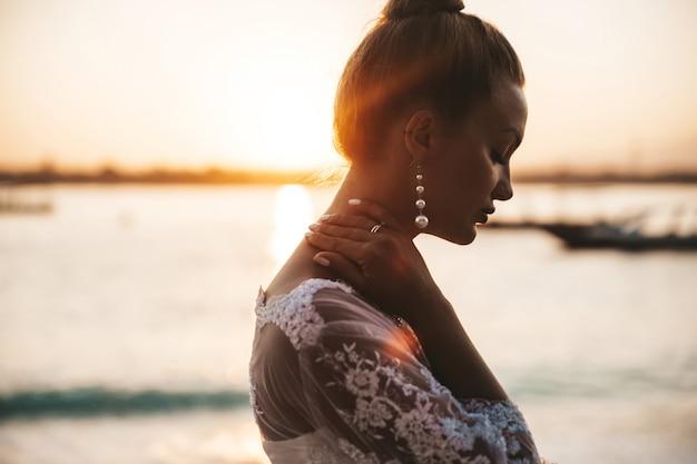 Piękna panna młoda pozuje na plaży za morzem o zachodzie słońca