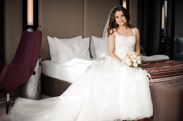 Piękna panna młoda siedzi na łóżku z kwiatami