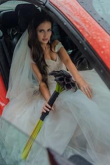 Piękna panna młoda siedzi w czerwonym samochodzie w białej sukni iz bukietem. koncepcja ślubu