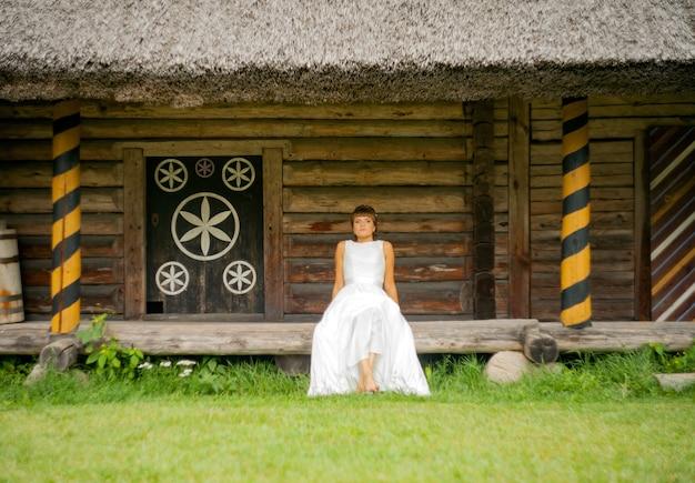 Piękna panna młoda siedzi w pobliżu domu w białej sukni. koncepcja ślub w stylu rustykalnym.