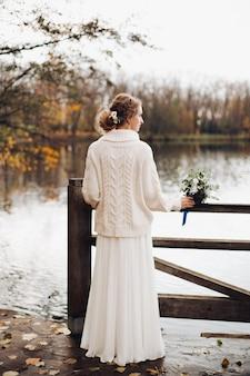 Piękna panna młoda stoi samotnie przy rzeczną gruszką w sukni i pulowerze