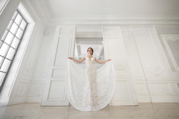 Piękna panna młoda stwarzających w sukni ślubnej na białym tle studio. lustro. sofa. bukiet. drzwi. żyrandol.