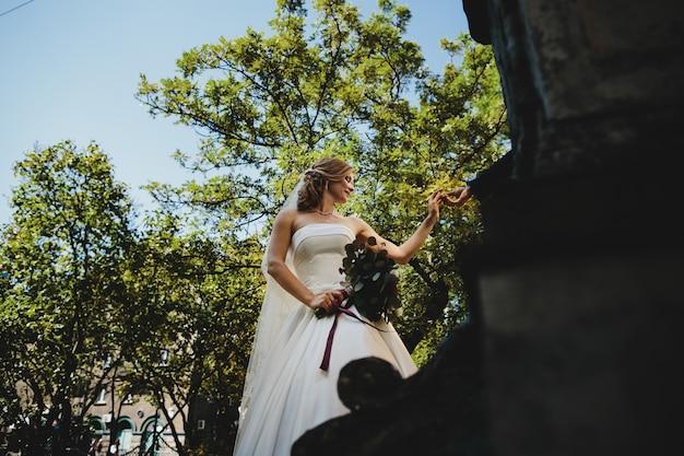 Piękna panna młoda trzyma bukiet ślubny i stoi w pobliżu budynku