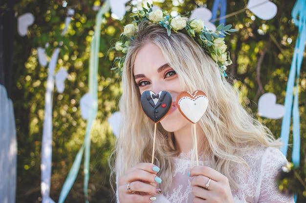 Piękna panna młoda trzyma ciasteczko na patyku w kształcie serca.