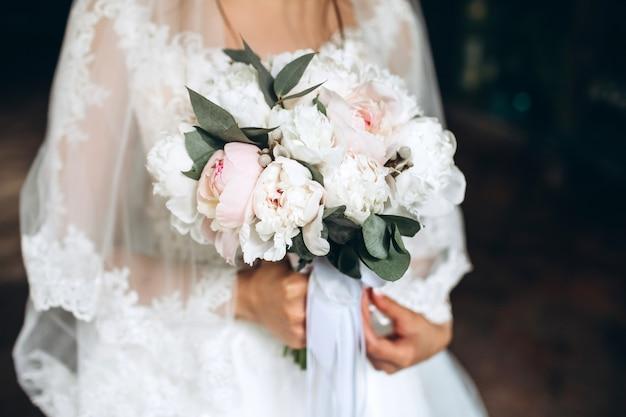 Piękna panna młoda trzyma w rękach bukiet ślubny z piwonii.