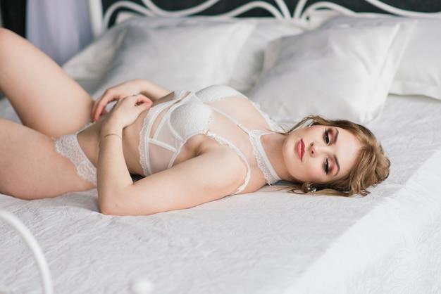Piękna panna młoda w białej bieliźnie. ostatnie przygotowania do ślubu. dziewczyna czeka na pana młodego.