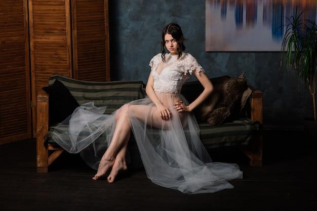 Piękna panna młoda w białej bieliźnie siedzi w swojej sypialni