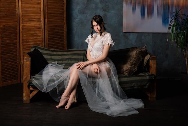 Piękna panna młoda w białej bieliźnie w jej sypialni w studio