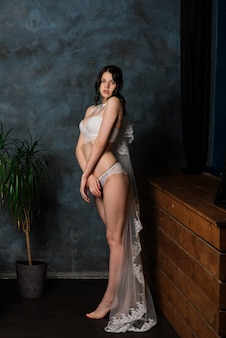Piękna panna młoda w białej bielizny obsiadaniu w jej sypialni