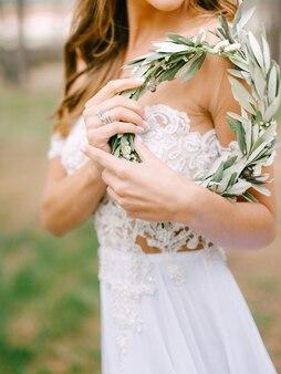 Piękna panna młoda w białej haftowanej sukience stoi bokiem i trzyma wieniec z zielonej oliwki