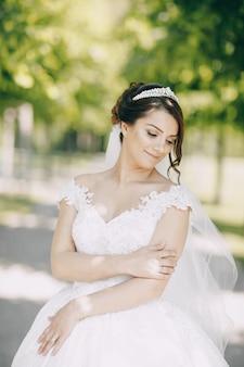 Piękna panna młoda w białej sukni i koronie na głowie w parku i trzymając bukiet