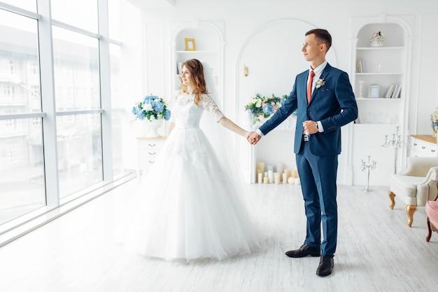 Piękna panna młoda w białej sukni i pana młodego w garniturze, pozowanie w białym wnętrzu studio, ślub