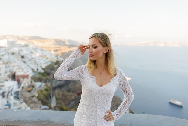 Piękna panna młoda w białej sukni pozuje na tle miasta thira, santorini.
