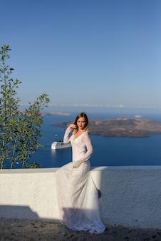 Piękna panna młoda w białej sukni pozuje na tle morza śródziemnego w thira, santorini.