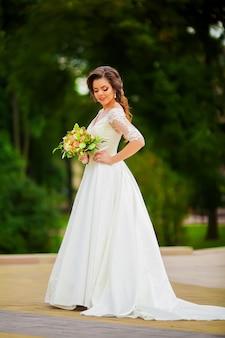 Piękna panna młoda w białej sukni w ogrodzie