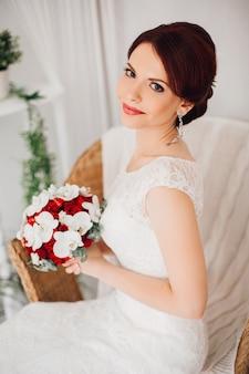 Piękna panna młoda w białej sukni z bukietem w ręce