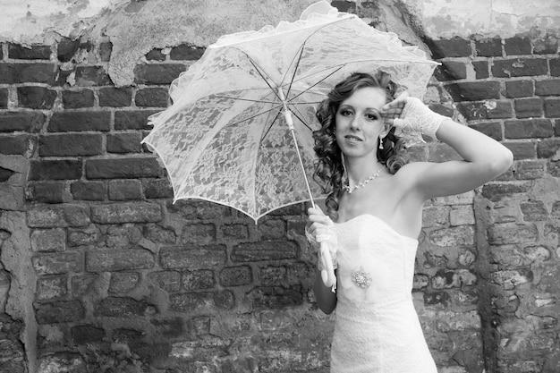 Piękna panna młoda w białej sukni z parasolem. fotografia czarno-biała