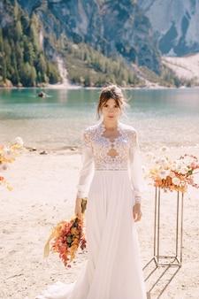 Piękna panna młoda w białej sukni z rękawami i koronką, z żółtym jesiennym bukietem, pozuje w lago di braies we włoszech