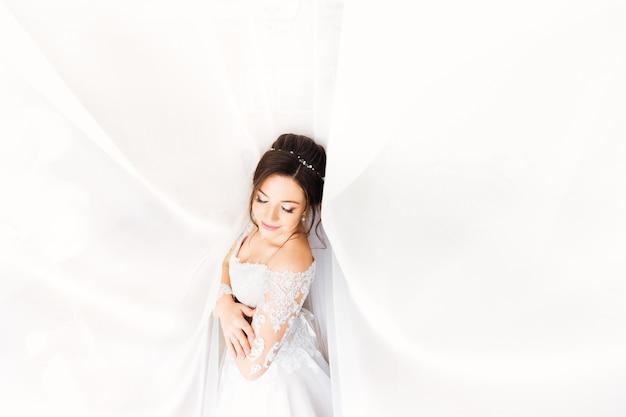 Piękna panna młoda w białej sukni zamknęła oczy na tle białych zasłon