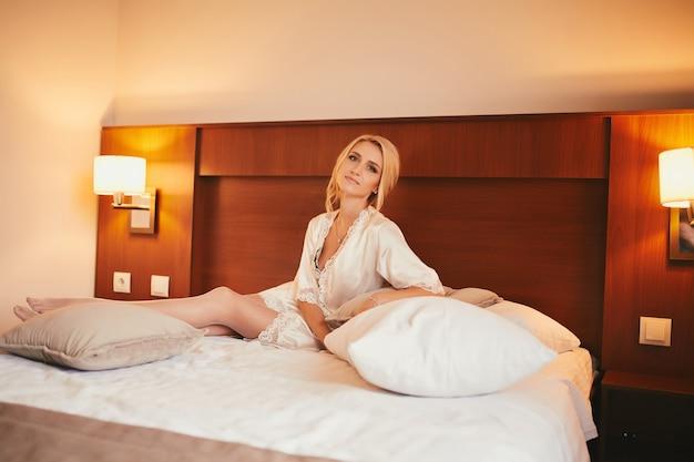 Piękna panna młoda w białym ślubie siedzi na dużym łóżku