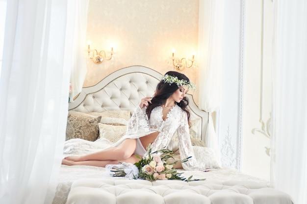 Piękna panna młoda w bieliźnie iz wieńcem kwiatów na głowie, rano przed ślubem. biały szlafrok panny młodej