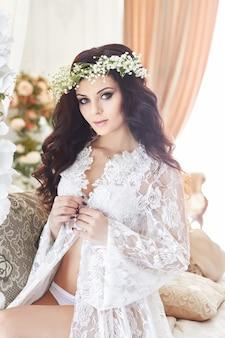 Piękna panna młoda w bieliźnie iz wieńcem kwiatów na głowie, rano przed ślubem.