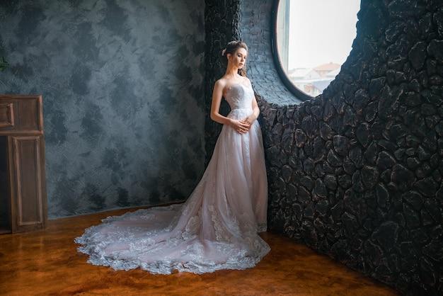 Piękna panna młoda w długiej sukni przy oknie