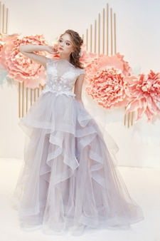 Piękna panna młoda w drogiej sukni ślubnej w obecności dużych sztucznych kwiatów. dziewczyna w białej sukni, doskonałe włosy i makijaż