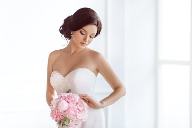 Piękna panna młoda w idealnym stylu. fryzura ślubna makijaż luksusowa suknia ślubna i bukiet panny młodej
