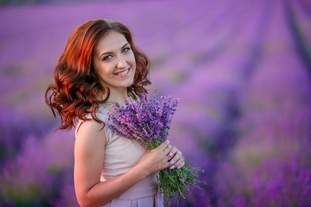 Piękna panna młoda w luksusowej sukni ślubnej w fioletowych kwiatach lawendy. fasonuje romantycznej stylowej kobiety z fiołkowym bukietem. nęcąca szczupła dziewczyna o zachodzie słońca nad lawendą czeka na pana młodego - prowansja francja