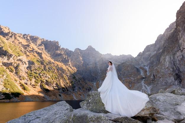 Piękna panna młoda w luksusowej sukni stoi na kamieniu w pobliżu góralskiego jeziora w ciepły słoneczny dzień