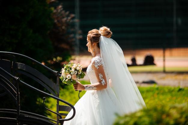 Piękna panna młoda w modnej sukni ślubnej na naturalnym tle. oszałamiająca młoda panna młoda jest niezwykle szczęśliwa. dzień ślubu