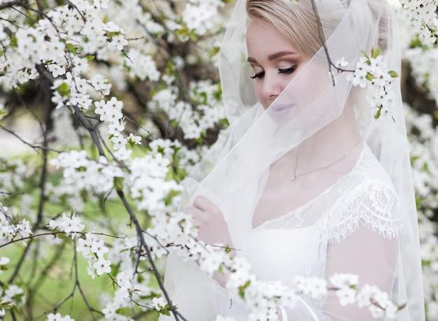 Piękna panna młoda w sukni ślubnej i koronkowym welonie na naturze. piękny model dziewczyny w białej sukni ślubnej.