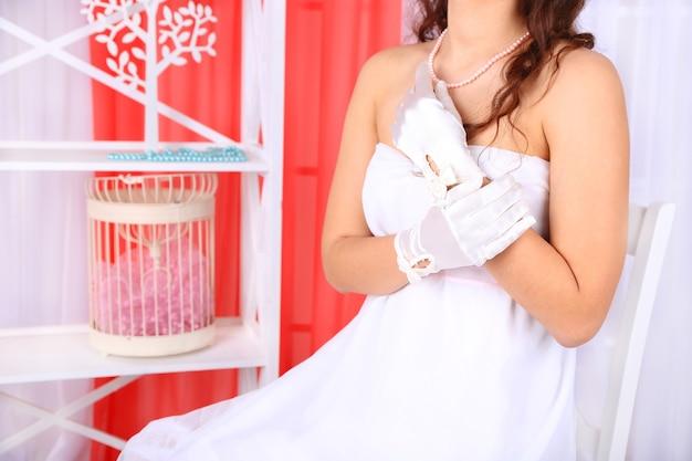 Piękna panna młoda w sukni ślubnej i rękawiczkach, zbliżenie, na wnętrze domu