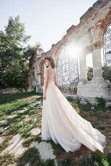 Piękna panna młoda w sukni ślubnej, która jest fotografowana w dniu ślubu w pobliżu starego zamku.