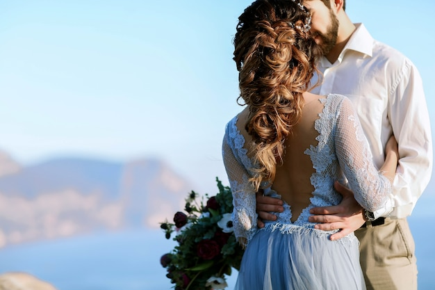 Piękna panna młoda w sukni ślubnej moda całuje w pobliżu skał