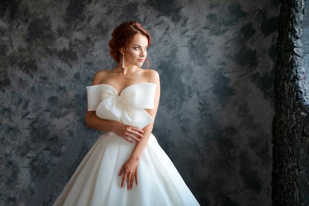 Piękna panna młoda w sukni ślubnej, pięknym makijażu i stylizacji